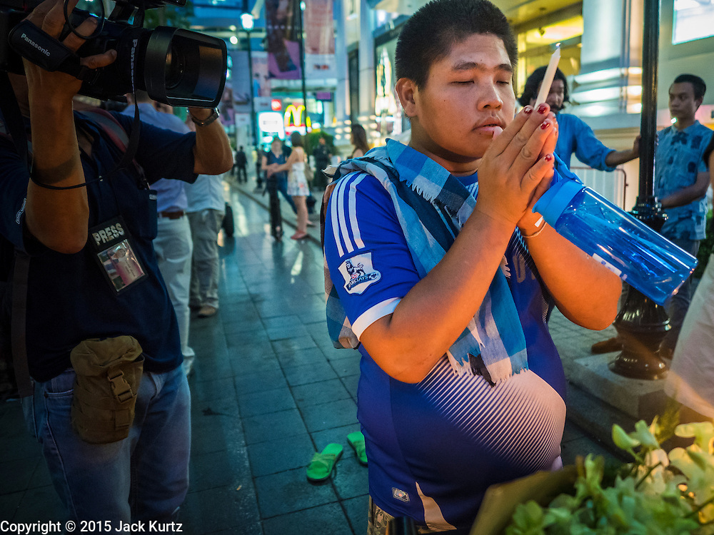 18 AUGUST 2015 - BANGKOK, THAILAND: A man prays at a makeshift memorial in front of Erawan Shrine, which was damaged by a bomb Monday night. An explosion at Erawan Shrine, a popular tourist attraction and important religious shrine in the heart of the Bangkok shopping district, killed at least 20 people and injured more than 120 others, including foreign tourists, during the Monday evening rush hour. Twelve of the dead were killed at the scene. Thai police said an Improvised Explosive Device (IED) was detonated at 18.55. Police said the bomb was made of more than six pounds of explosives stuffed in a pipe and wrapped with white cloth. Its destructive radius was estimated at 100 meters.    PHOTO BY JACK KURTZ