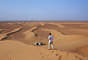 Young man walks down the sand dunes in the Sahara Desert, Morocco