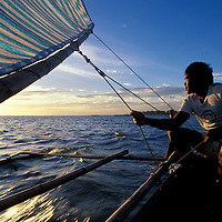 Man sails outrigger boat off Panay Island at sunset in the Philippines