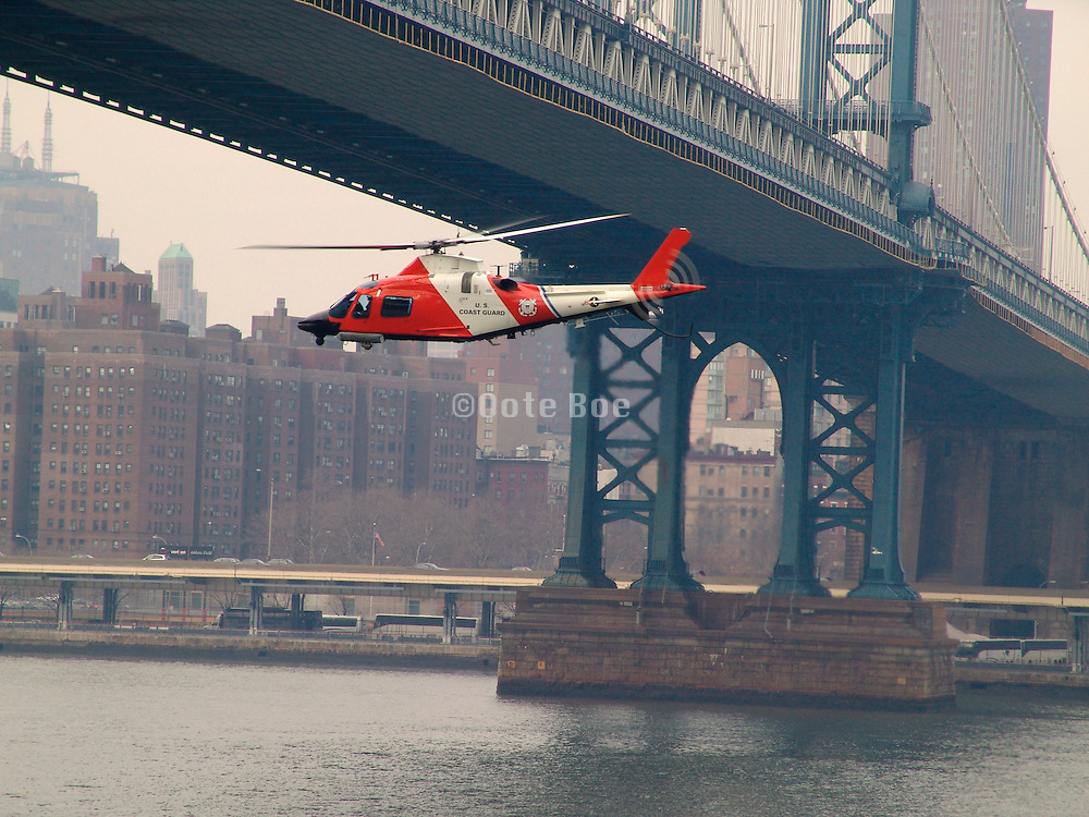 U.S. coast guard helicopter flying under the Manhattan bridge.
