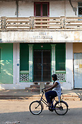A girl rides her bicycle past a Colonial house, Pondicherry, India. Pondicherry now Puducherry is a Union Territory of India and was a French territory until 1954 legally on 16 August 1962. The French Quarter of the town retains a strong French influence in terms of architecture and culture.