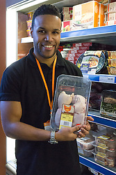 "© Licensed to London News Pictures. 19/12/2014. London, UK. A member of staff holds chicken costing 49p in the meat section of the Community Shop. The Community Shop opened this week in Gipsy Hill, South London and is a ""social supermarket"", which sells heavily-discounted surplus food that would otherwise be thrown away. Food is received from retail brands such as Marks & Spencer, Asda, Tesco, Innocent and Muller and many more. The shop works on a membership basis only, serving residents who are on income support and aimed at people who are in work, but low waged and for those working hard to find a job. Photo credit : Vickie Flores/LNP"