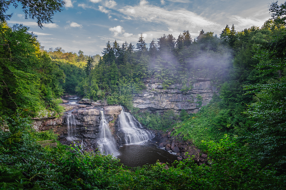 Small pockets of fog sweep in and out, hanging over the iconic Blackwater Falls of West Virginia on an early summer morning.