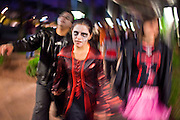"""Oct. 30, 2009 -- PHOENIX, AZ: PRISCILLA MARQUEZ leads a group of Zombies into a shopping area during the Zombie Walk in Phoenix Friday. About 200 people participated in the first """"Zombie Walk"""" in Phoenix, AZ, Friday night. The Zombies walked through downtown Phoenix """"attacking"""" willing victims and mixing with folks going to the theatre and downtown sports venues.  Photo by Jack Kurtz"""