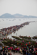 """View from a hill top to the open """"Mysterious Sea Road"""" at Hoedong shore (Jindo island). Jindo is the 3rd biggest island in South Korea located in the South-West end of the country and famous for the """"Mysterious Sea Route"""" or """"Moses Miracle"""". Every spring thousands flock to the shores of Jindo to walk the mysterious route that stretches roughly three kilometers from Hoedong to the distant island of Modo. Materializing from the rise and fall of the tides, the divide can reach as wide as forty meters."""