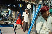 A woman walks past rickshaw wallahs in Sitaram Bazar, Old Delhi, India