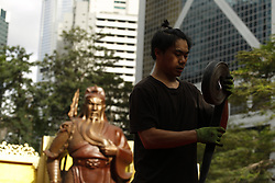 June 25, 2017 - Hong Kong, CHINA - Behind the worker stands 6 meter tall ( 20ft ) bronze statue of Guan Gong ( Warrior God ), a much worshipped Chinese folk-hero which is installed at the park in Central to celebrate 20th anniversary of the Hong Kongs HANDOVER to China. June 25, 2017.Hong Kong.ZUMA/Liau Chung Ren (Credit Image: © Liau Chung Ren via ZUMA Wire)