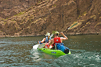 A couple in a tandem kayak paddles up the currents of The Colorado River in The Black Canyon, Nevada.