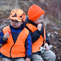 Liam and Jackson Queneau, 5 and 3, take a breather from hunting with dad to share a fruit rollup.