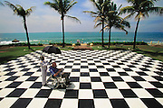 Colombo, Sri Lanka..Sir Arthur C. Clarke sits in his wheelchair (he has post-polio syndrome) upon a checkerboard-patterned area outside the grand seaside Galle Face Hotel in Colombo, Sri Lanka. Clarke wrote 3001, the last book of his acclaimed science fiction series while living in this hotel. (He wrote 2001 while living in the Chelsea Hotel in New York City). Protecting Clarke from the fierce noon sun, is the hotel doorman, Kattarapatte Chadthu Kuttan, 70, who has worked at the Galle Face Hotel for 58 years, since age 12. (2001) Best known for the book 2001: A Space Odyssey. MODEL RELEASED