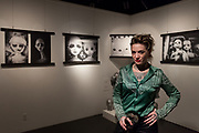 Portrait of photographer  Celeste Urreaga  in front of her images in an exhibition at the Instituto Cervantes i Tokyo, Ichigaya, Tokyo, Japan. Wednesday November 21st 2018