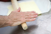 Making puff pastry at a bakery Baker rolls the dough