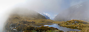 Panoramic view of tarn and clouds at MacKinnon Pass, Milford Track, Fiordland National Park, New Zealand