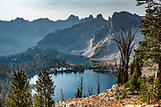 Smoky haze over Twin Lakes (8858 feet elevation) in Sawtooth Wilderness, Blaine County, Idaho, USA. On October 6-7, 2020, starting from Tin Cup Trailhead, I hiked a clockwise loop 20 miles with an overnight stay at idyllic Twin Lakes. The first day to Twin Lakes was a moderate 7.4 miles with 2090 feet gain. The second day returned via Toxaway Lake and Farley Lake for 12.5 miles with 1260 feet up and 2940 feet down. For the most dramatic scenic build-up, I recommend backpacking 3 days counterclockwise staying at Toxaway Lake then Twin Lakes. (On a 2007 backpacking trip in August, we enjoyed staying 2 nights at Alice Lake and day-hiked to Toxaway.) The Sawtooth Range (part of the Rocky Mountains) are made of pink granite of the 50 million year old Sawtooth batholith. Sawtooth Wilderness, managed by the US Forest Service within Sawtooth National Recreation Area, has some of the best air quality in the lower 48 states (says the US EPA).