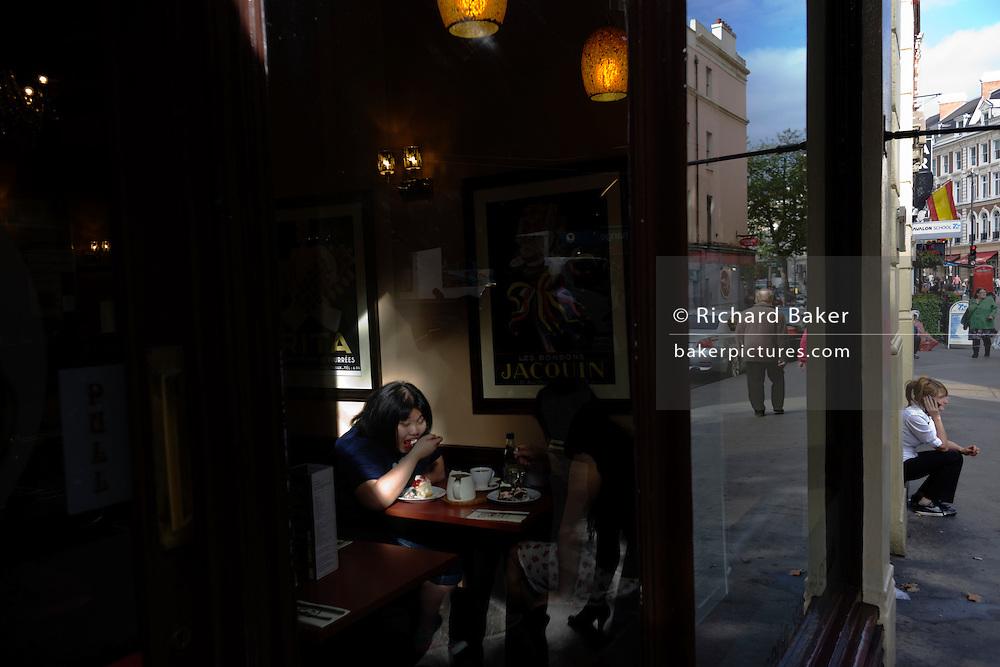 Seen through a street window, two women eat fattening cakes in a sunlit London cafe.