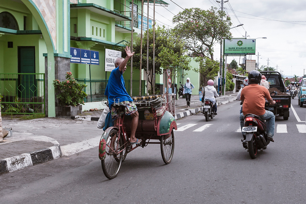 A bekak rider waves as he rides past in the streets of Yogyakarta.