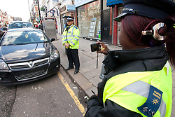 Traffic warden with colleague taking photos to record a parking offence in Green Lanes Haringey London UK