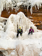 A boy and girl sit on an ice formation at the Apostle Island Ice Caves, Makwike Bay, near Bayfield, Wisconsin, on a cold February day.