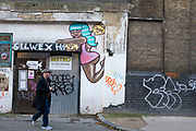 Street art at the entrance to a warehouse in Spitalfields, London, UK. The graffiti depicts a scantily clad black woman climbing the doors.