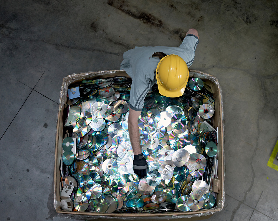 Worker reaching in a crate of compact disk media at data recycle center, top view.
