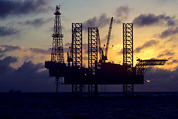 Stock photo of a jack up drilling rig at dusk off of the Gulf of Mexico