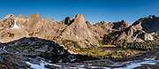 """In Cirque of the Towers, Pingora Peak rises above Lonesome Lake at sunrise, seen from Jackass Pass, in Bridger Wilderness, Wind River Range, Bridger-Teton National Forest, Rocky Mountains, Wyoming, USA. We backpacked to Big Sandy Lake Campground (11 miles round trip with 1000 feet gain). Two hours before sunrise, I departed from Big Sandy Lake to reach Jackass Pass viewpoint for Cirque of the Towers and Lonesome Lake (6.5 miles round trip, 1860 ft gain) on the Continental Divide Trail. The Continental Divide follows the crest of the """"Winds"""". Mostly composed of granite batholiths formed deep within the earth over 1 billion years ago, the Wind River Range is one of the oldest mountain ranges in North America. These granite monoliths were uplifted, exposed by erosion, then carved by glaciers 500,000 years ago to form cirques and U-shaped valleys. This image was stitched from multiple overlapping photos."""