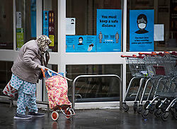 © Licensed to London News Pictures. 02/02/2021. London, UK. An elderly lady wearing a face mask walks past social distancing signs in West Ealing, West London, where a new South African variant of coronavirus has ben discovered. Door-to-door delivery of free home test kits is to start in the area in an attempt to slow the spread of the more aggressive strain of the virus. Photo credit: Ben Cawthra/LNP