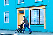 Man wheels child in stroller along the street in Courtmacsherry, County Cork, Ireland