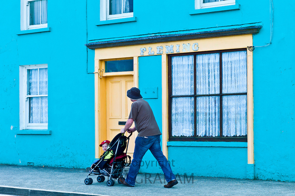 Man wheels child in stroller along the street in Courtmacsherry, County Cork, Ireland