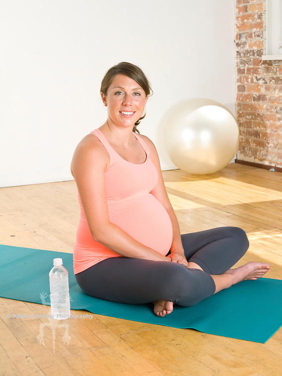 A pregnant woman (20-30 years old) sits on a yoga mat, with a bottle of water.