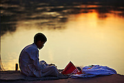 A Hindu Student studying vedas on the bank of river Ganga (Ganges) at sunset.