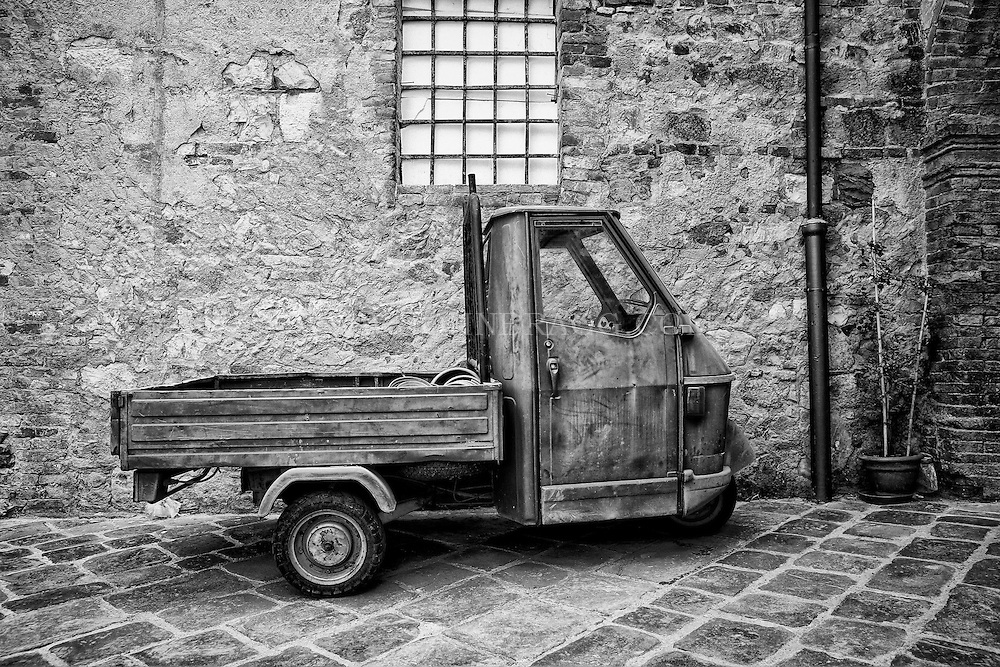 Black and white image of a little truck resting on the streets of San Quirico d'Orcia, Italy.