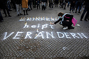 """A participant lays a candle on the writing """"Remembering means changing"""" during a memorial demonstration, commemorating the anniversary to the Hanau terror attack, in Berlin, Germany, February 19, 2021. About 800 participants took part in the event in remembrance of the Hanau shootings, in which ten people were killed and five others wounded. The shooting spree was committed on February 19, 2020 by a far-right extremist targeting two shisha bars and kiosks at the Hessian city of Hanau near Frankfurt. The gunman was identified as 43-year-old Tobias Rathjen. The majority of the victims were Germans with migrant backgrounds, among the victims was also the perpetrator's mother. (Photo by Omer Messinger)"""