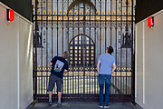 A day after British Prime Minister Boris Johnson successfully asked the Queen to suspend (prorogue) Parliament in order to manoeuvre his Brexit deal with the EU in Brussels, two tourists peer through the railings Royal Entrance at the base of Victoria Tower at the Houses of Parliament, on 29th August 2019, in Westminster, London, England.