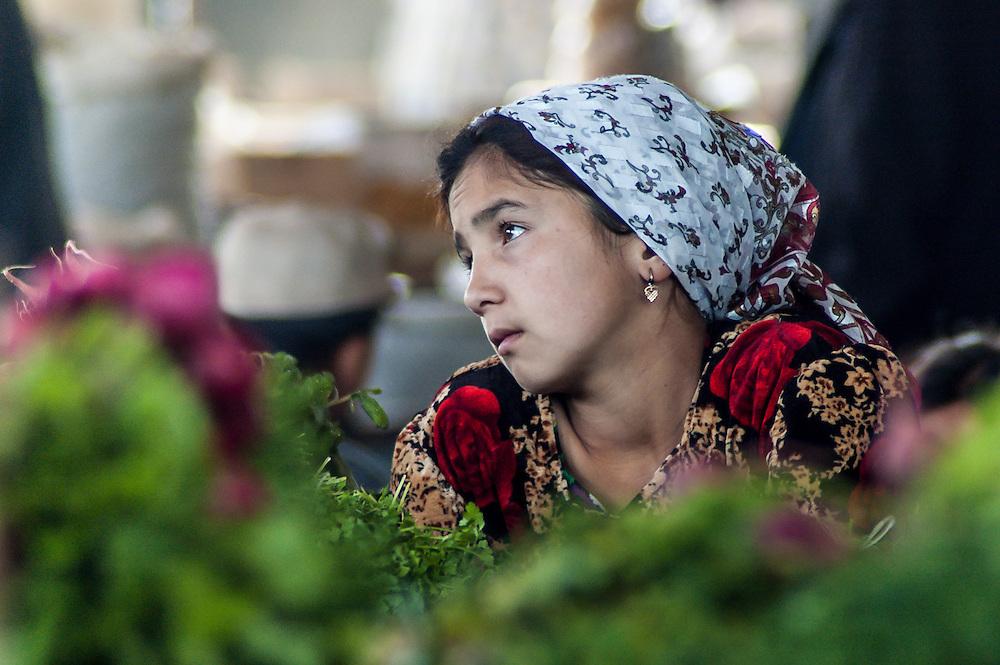 Portrait of a young Tajik girl looking on in boredom at market activities in western Tajikistan