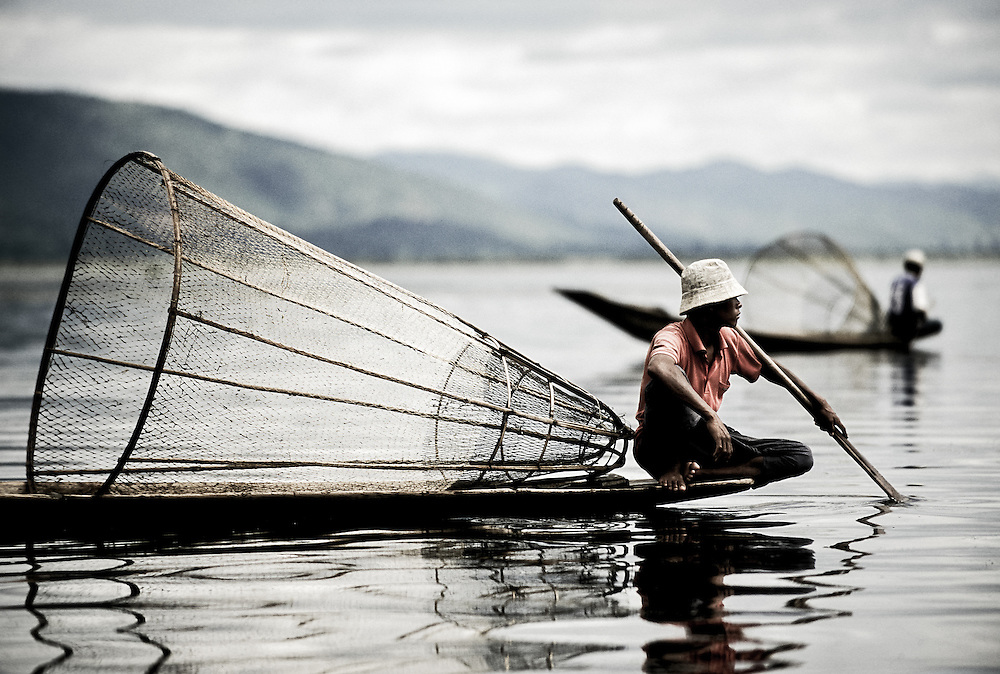 USE ARROWS ← → on your keyboard to navigate this slide-show<br /> <br /> Inle Lake, Myanmar - May 2006<br /> Burmese fishermen drive a boat in lake Inle. <br /> The fishermen are known for their technique of rowing wrapping one of the legs around the oar to relieve and free arms for fishing. <br /> Photo: Ezequiel Scagnetti