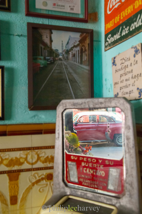 Close up of wall with photography and reflection of car in mirror, Havana, Cuba