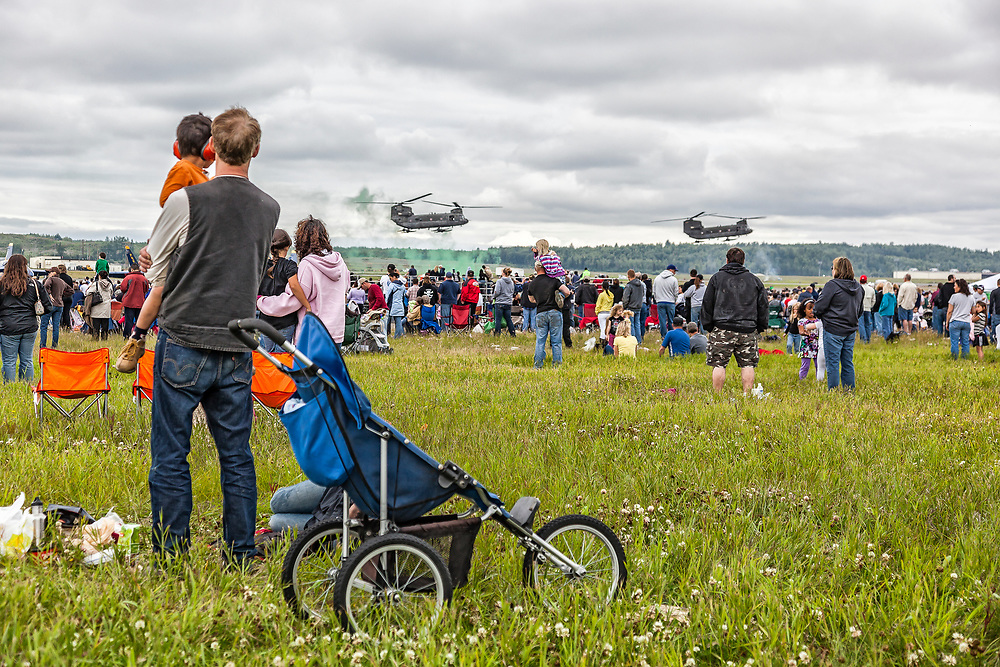 Alaska.  A crowd of visitors, including a man with a stroller and young children, watch a staged  Army assault demonstration with two Boeing Chinook CH-47 helicopters at Elmendorf AFB during a military base open house in 2010.