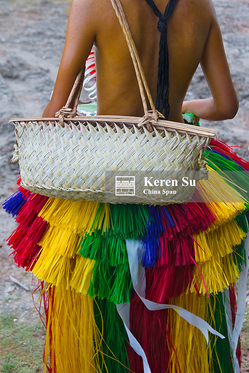 Girl wearing grass skirt carrying purse made from banana leaves, Yap Island, Federated States of Micronesia