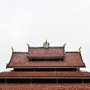 The multi-layered tiled roof of a wat (Buddhist temple) in Luang Prabang, Laos, against an overcast sky. The points of the roof are adorned for chofah's, a depiction of Garuda, the half-man half-bird vehicle of the Hindy god Vishnu.