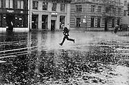 Man running across Paradepatz, the centre of Switzerland's banking industry, during a sudden heavy rain storm.
