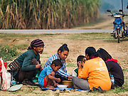 02 FEBRUARY 2016 - NONG LAN, KANCHANABURI, THAILAND: Migrant sugar cane workers eat their breakfasts on the edge of the fields they were hired to harvest. Thai sugar cane yields are expected to drop by about two percent for the 2015/2016 harvest because of below normal rainfall. The size of the crop is expected to increase slightly though because farmers planted more sugar cane acreage this year. Thailand is the second leading exporter of sugar in the world. Thai sugar growers are hoping a good crop would make up for shortages in global markets caused by lower harvests in Brazil and Australia, where sugar yields have been stunted by drought. Because of the drought in Thailand, sugar exports are expected to drop by up to 20 percent, contributing to a global sugar shortage. The drought is is also hurting the quality of Thai sugar, because sugarcane grown in drought is less sweet than normal so mills need to process more cane to make the same amount of sugar. Thai sugar farmers have lost 20 percent to 30 percent of their output this year because of the drought.         PHOTO BY JACK KURTZ