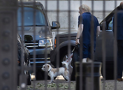 © Licensed to London News Pictures. 31/05/2020. London, UK. Prime Minister Boris Johnson holds a tennis racket as he arrives back in Downing Street with his dog Dilyn after going out for exercise. The government have announced new measures from Monday to allow groups of six people to meet outdoors. Photo credit: Peter Macdiarmid/LNP
