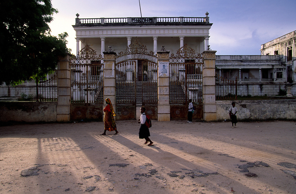 People passing by the facade of Ilha de Mozambique hospital