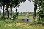 Nederland, Millingen, 20-5-2014Scholieren fietsen over een smalle weg in de polder van school naar huis. Zij zijn kwetsbaar in het verkeer waar ze niet op een apart fietspad kunnen rijden.Foto: Flip Franssen/Hollandse Hoogte