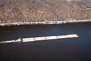 A Marquette Transportation pusher boat drives barges upstream on the Mississippi River near Prairie du Chien, Wisconsin, USA.