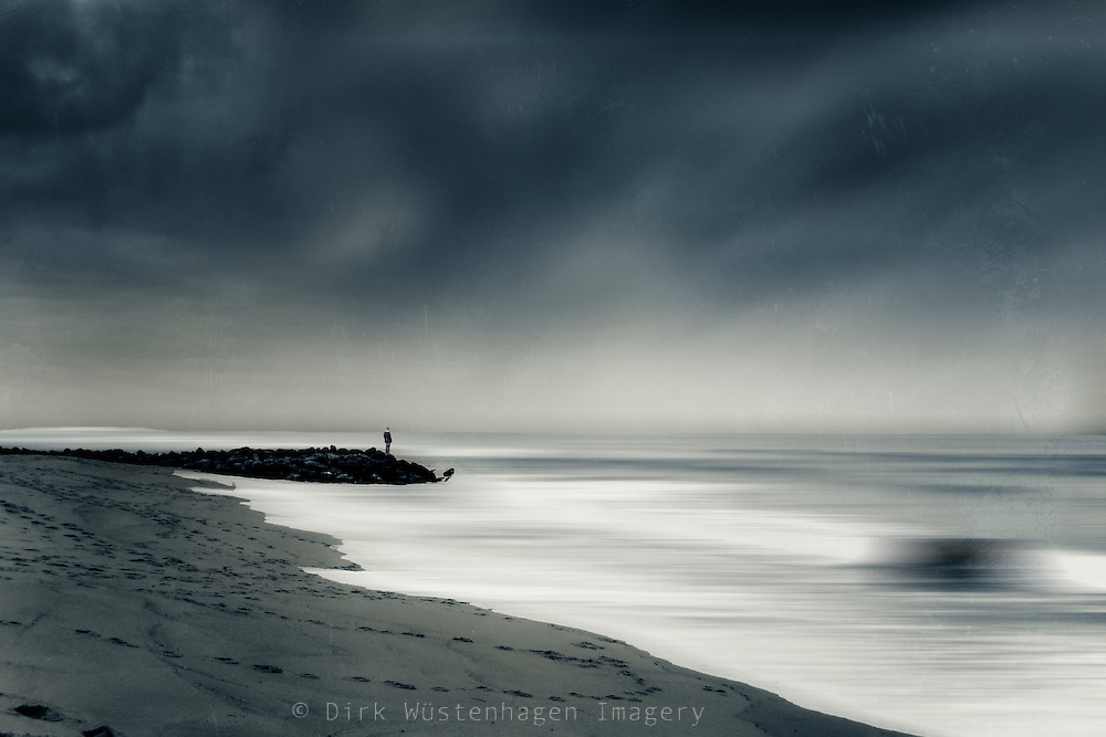 Moody abstract seascape with a man standing on a levee.