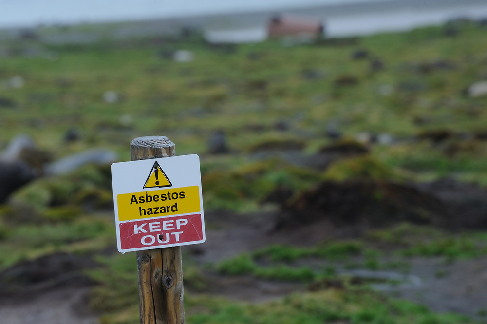 Asbestos Hazard Keep out signs at the old Stromness whaling station. Stromness, Stromness Bay, South Georgia, South Atlantic. 20Feb16.