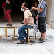 People standing on a street covered with tear dust thrown extensively by riot police during a protest in Athens' Syntagma (Constitution) square, June 29, 2011
