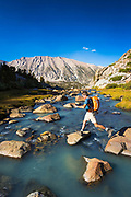 Hiker crossing stream in Sam Mack Meadow, John Muir Wilderness, Sierra Nevada Mountains, California USA